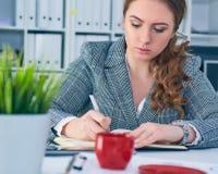 La mujer de negocios seria joven en chaqueta escribe en el tablero en el lugar de trabajo en la oficina Fotos de archivo libres de regalías