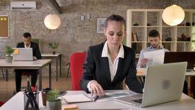 La mujer de negocios seria joven está mirando el ordenador portátil y gráficos en oficina, mirando en la cámara, sonriendo, estab metrajes