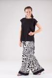 La mujer de negocios sonriente atractiva se vistió en pantalones blancos y negros anchos y blusa negra Fotografía de archivo libre de regalías