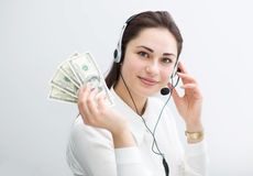 La mujer de negocios sonriente en auriculares sostiene billetes de banco disponibles Fotos de archivo libres de regalías