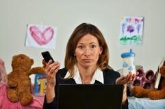 La mujer de negocios sostiene el teléfono y la botella de bebé Fotos de archivo libres de regalías