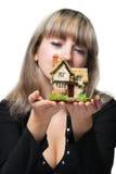 La mujer de negocios sostiene la pequeña casa Foto de archivo