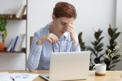 La mujer de negocios subrayada con exceso de trabajo que sostiene los vidrios siente la fatiga visual fotografía de archivo