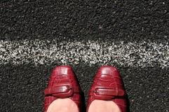 La mujer de negocios toca con la punta del pie la línea corporativa Foto de archivo