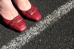 La mujer de negocios toca con la punta del pie la línea corporativa Fotografía de archivo