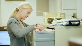 La mujer de negocios toma una carpeta con los documentos de un cajón en estilo retro almacen de metraje de vídeo