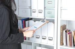 La mujer de negocios toma una carpeta que esté en el estante en la oficina Imagen de archivo libre de regalías