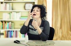 La mujer de negocios toma una píldora que se sienta en el escritorio Fotos de archivo libres de regalías