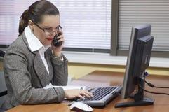 La mujer de negocios trabaja detrás del ordenador Fotografía de archivo libre de regalías