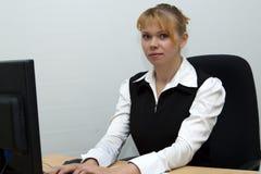 La mujer de negocios trabaja en el ordenador en oficina Imagenes de archivo