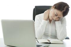La mujer de negocios triguena joven tiene cuello del dolor Foto de archivo