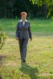 La mujer de negocios de una edad está caminando en el parque Fotografía de archivo libre de regalías