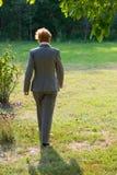 La mujer de negocios de una edad está caminando en el parque Imagen de archivo