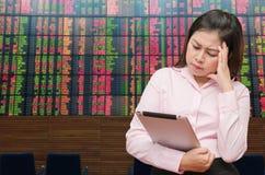 La mujer de negocios ve la pantalla de la tableta para la pérdida valorar y sentir la tensión del dolor con el tablero común Foto de archivo libre de regalías