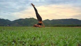 La mujer de la opinión inferior del primer lleva a cabo actitud de la yoga contra las colinas verdes