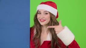 La mujer de Papá Noel mira furtivamente mostrando un finger en una cartelera de publicidad azul del tablero Pantalla verde Cierre almacen de metraje de vídeo