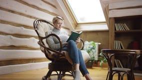 La mujer de pelo corto rubia lee un libro en el ático almacen de metraje de vídeo