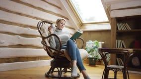 La mujer de pelo corto rubia lee un libro y bebe el café en el ático metrajes