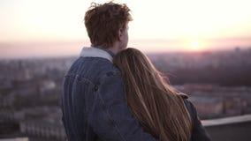 La mujer de pelo largo joven y el hombre dirigido rojo vinieron en el alto tejado para mirar en la ciudad en la puesta del sol Ob metrajes