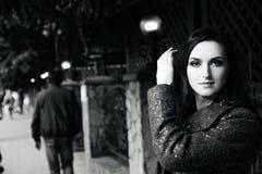 La mujer de pelo oscuro asombrosa se está colocando en la calle y está mirando la cámara Retrato blanco y negro de atractivo Imagen de archivo