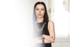La mujer de pelo oscuro magnífica en un vestido negro y una joyería masiva del oro se coloca en el cuarto blanco Fondo Imágenes de archivo libres de regalías