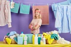 La mujer de pelo rubio en camiseta rosada en guantes rosados es feliz pues ella ha acabado su quehacer doméstico imagen de archivo libre de regalías
