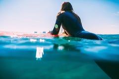 La mujer de la persona que practica surf es se relaja en la tabla hawaiana en el océano Persona que practica surf y océano Fotografía de archivo