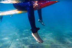 La mujer de la persona que practica surf se está sentando en la tabla hawaiana, bajo el agua Persona que practica surf y océano Foto de archivo