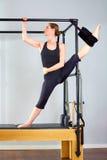 La mujer de Pilates en las piernas partidas de Cadillac estira ejercicio Imagen de archivo