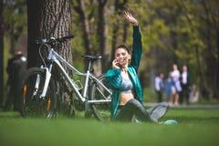 La mujer de reclinación con la bici está saludando alguien foto de archivo libre de regalías