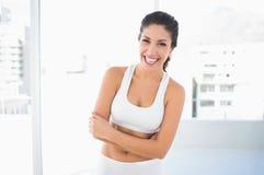 La mujer de risa apta en ropa de deportes con los brazos cruzó la mirada de la cámara Fotografía de archivo