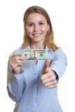 La mujer de risa con el dólar observa mostrar el pulgar para arriba Imagen de archivo libre de regalías