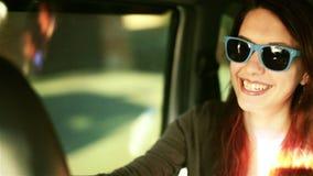 La mujer de risa en gafas de sol dentro de una alegría del coche monta almacen de video