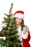 La mujer de Santa cerca del árbol de abeto sostiene el regalo de la Navidad fotos de archivo