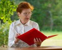 La mujer de una empresaria en edad mira documentos Fotografía de archivo libre de regalías