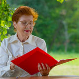 La mujer de una empresaria en edad mira documentos Fotos de archivo