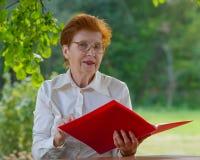 La mujer de una empresaria en edad mira documentos Fotos de archivo libres de regalías