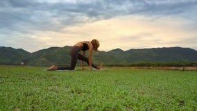 La mujer de la visión inferior lleva a cabo la posición de la yoga respecto a prado verde