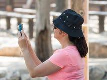 La mujer de Yong se coloca en un día soleado y aprende tomar imágenes con una cámara Imágenes de archivo libres de regalías