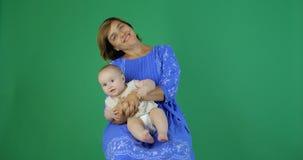 La mujer del  ТЬdel  Ð 'ОТРde Ð' ОРРmueve alegre al niño encantador mientras que se sienta, cámara lenta metrajes