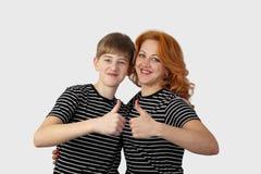 La mujer del adolescente y del pelirrojo muestra los pulgares encima del gesto Imagen de archivo