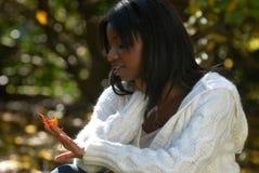 La mujer del African-American mira en una hoja Imagen de archivo libre de regalías