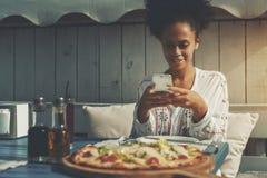 La mujer del Afro está tirando la pizza en su teléfono móvil Imagen de archivo