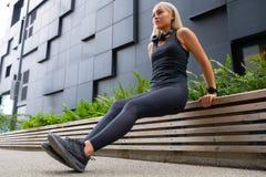 La mujer del ajuste que hace el tríceps sumerge al aire libre en ciudad moderna foto de archivo libre de regalías