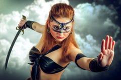 La mujer del Amazonas con el pelo rojo largo que sostiene una espada Imagen de archivo libre de regalías