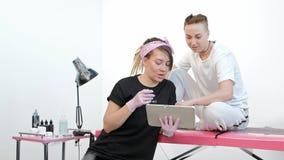 La mujer del amo del tatuaje discute bosquejo con el cliente, muestra imágenes en la tableta en estudio almacen de video