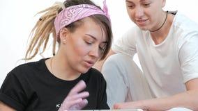 La mujer del amo del tatuaje discute bosquejo con el cliente, muestra imágenes en la tableta en estudio almacen de metraje de vídeo