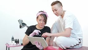 La mujer del amo del tatuaje discute bosquejo con el cliente, muestra imágenes en la tableta en estudio metrajes