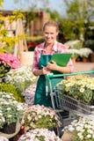 La mujer del centro de jardinería puso el carro en conserva de las flores Foto de archivo libre de regalías