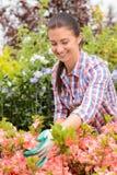 La mujer del centro de jardinería se coloca en la sonrisa del macizo de flores Foto de archivo libre de regalías